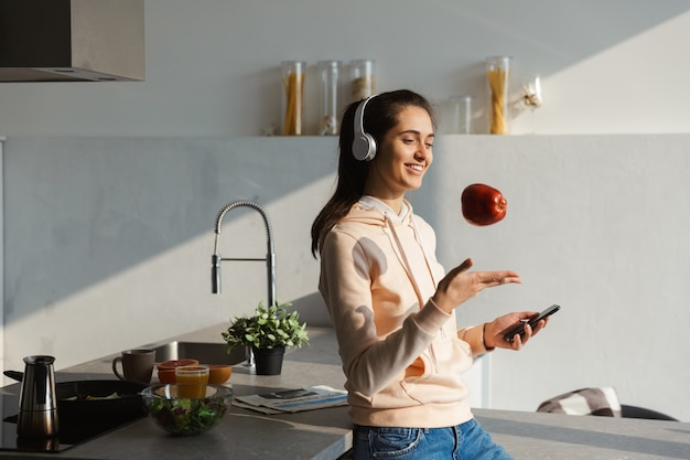 Vrolijk jong meisje luisteren naar muziek met een koptelefoon in de keuken thuis, een appel eten, mobiele telefoon te houden
