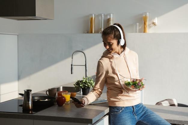 Vrolijk jong meisje, luisteren naar muziek met een koptelefoon in de keuken thuis, salade eten uit een kom