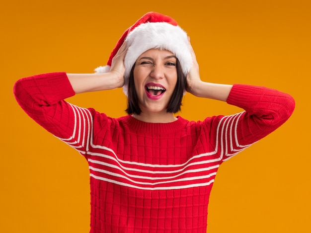 Vrolijk jong meisje met een kerstmuts die naar een camera kijkt die knipoogt en de handen op het hoofd houdt geïsoleerd op een oranje achtergrond