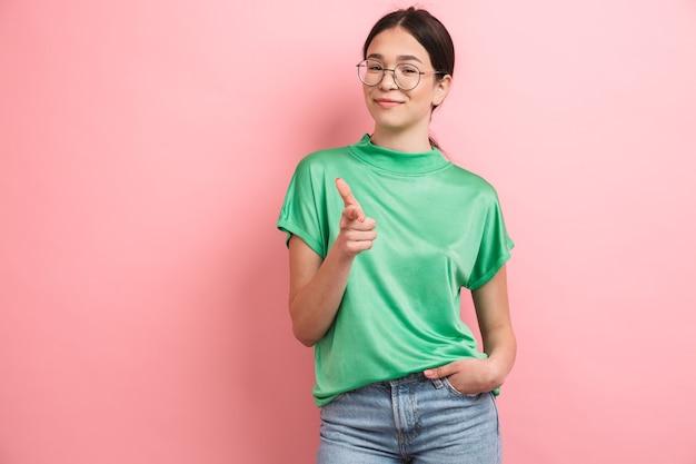 Vrolijk jong meisje met een ronde bril die lacht en met de vinger naar de voorkant wijst, geïsoleerd over roze muur