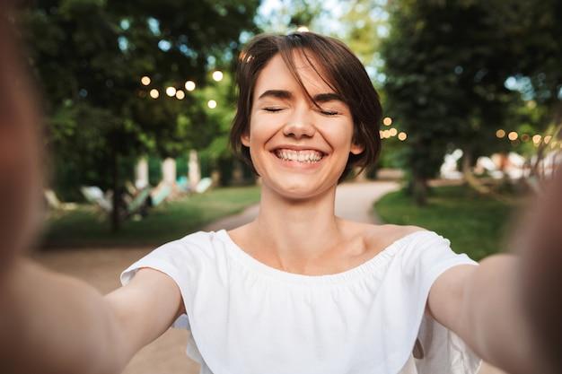 Vrolijk jong meisje met gesloten ogen het nemen van een selfie