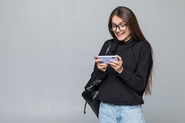 Vrolijk jong meisje met het spel van het rugzakspel met mobiele telefoon dat op witte muur wordt geïsoleerd.