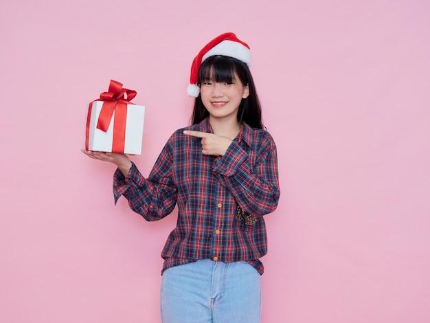 Vrolijk jong meisje met kerstmuts in geruite hemd met geschenkdoos te houden