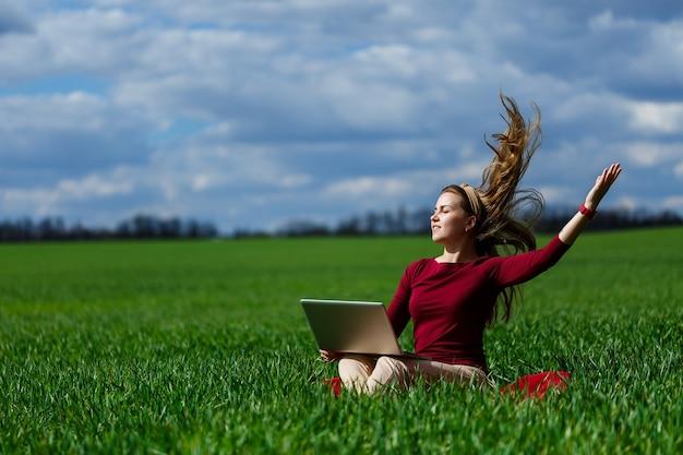 Vrolijk jong meisje op het gras met een laptop op haar schoot. hij hief zijn handen omhoog en lachte. geluk in de levensstijl van een klassieke student. werk aan de natuur. rust na een goede werkdag.
