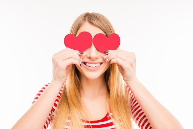 Vrolijk jong meisje verbergt haar ogen achter twee papieren harten