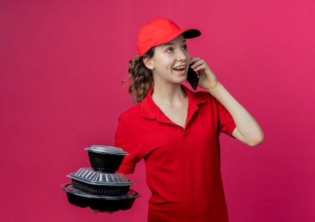Vrolijk jong, mooi bezorgmeisje met een rood uniform en een pet die aan de telefoon praat en voedselcontainers vasthoudt die naar de zijkant op de karmozijnrode ruimte kijken