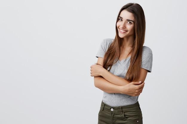 Vrolijk jong mooi donkerbruin kaukasisch studentenmeisje die met lang haar in toevallige modieuze uitrusting helder glimlachen, samen houdend handen, stellend voor universitaire afstudeerfoto in lichte muur.