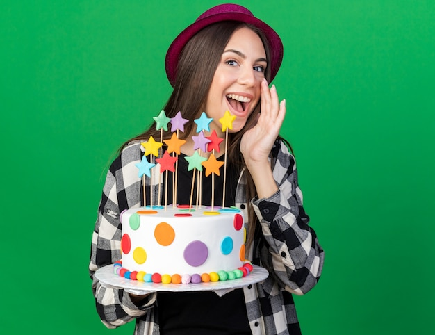 Vrolijk jong mooi meisje met feestmuts met cake die iemand belt