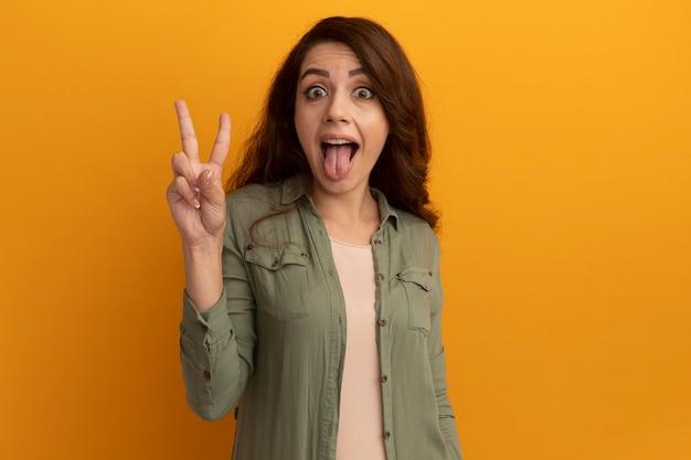 Vrolijk jong mooi meisje met olijfgroen t-shirt met tong en vredesgebaar geïsoleerd op gele muur met kopieerruimte