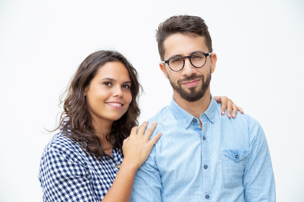 Vrolijk jong paar dat bij camera glimlacht
