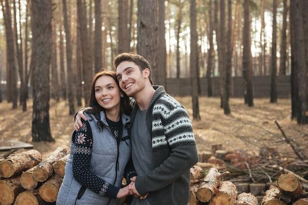 Vrolijk jong paar die omhoog terwijl het koesteren en het lopen in bos kijken