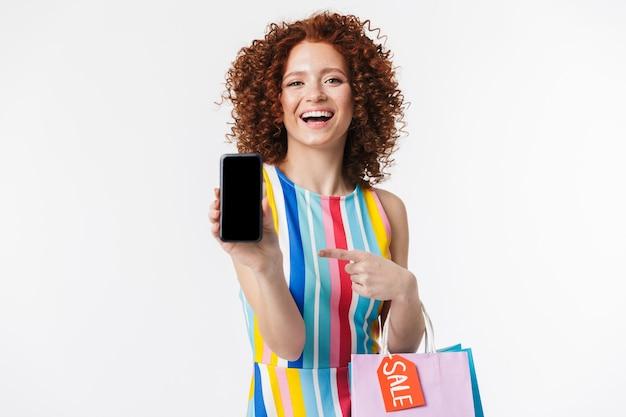 Vrolijk jong roodharig meisje dat een jurk draagt, boodschappentassen draagt die over een witte muur zijn geïsoleerd en een mobiele telefoon met een leeg scherm toont