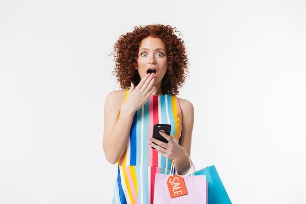 Vrolijk jong roodharig meisje dat jurk draagt, boodschappentassen draagt die over een witte muur zijn geïsoleerd, mobiele telefoon vasthoudt