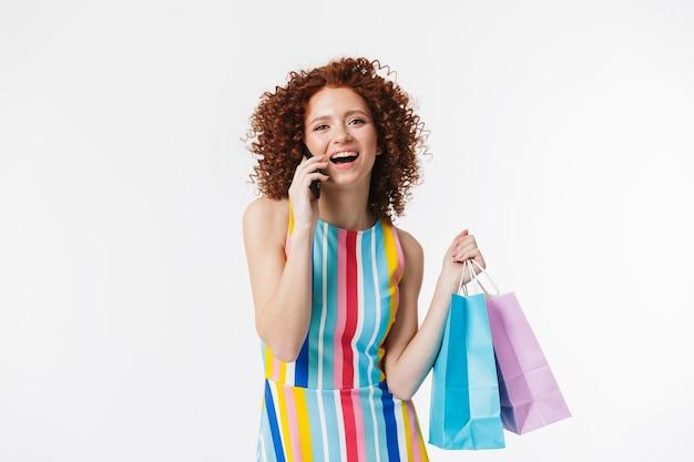 Vrolijk jong roodharig meisje in jurk, met boodschappentassen geïsoleerd over witte muur, pratend op mobiele telefoon
