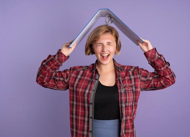 Vrolijk jong slavisch studentenmeisje houdt dossiermap boven haar hoofd