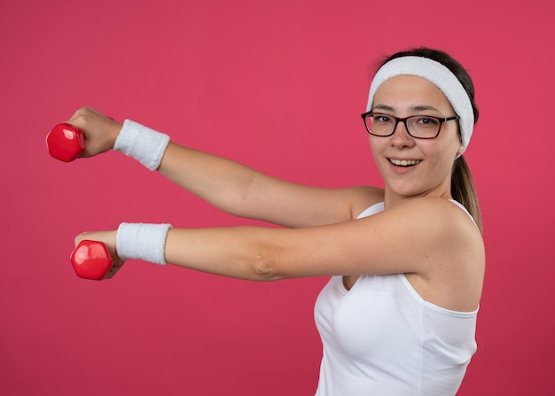 Vrolijk jong sportief meisje met een optische bril met een hoofdband en polsbandjes staat zijwaarts met halters