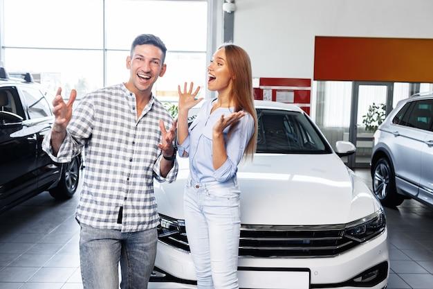 Vrolijk jong stel bij de dealer die een nieuwe auto binnen koopt