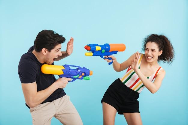 Vrolijk jong stel dat geïsoleerd staat, plezier heeft met waterpistolen