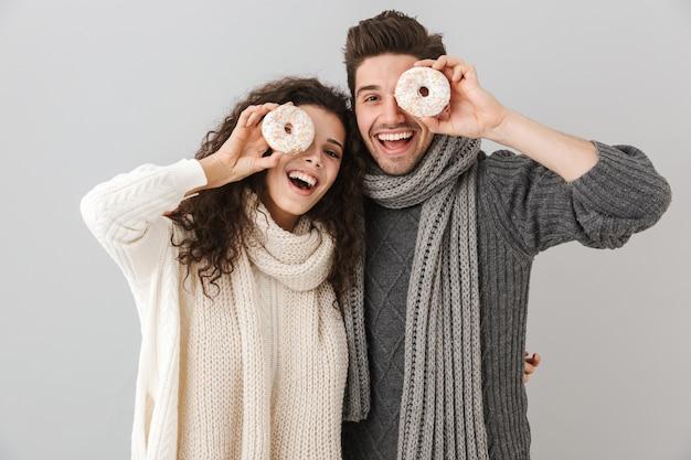 Vrolijk jong stel dat truien en sjaals draagt die zich geïsoleerd over grijze muur bevinden, die donuts tonen