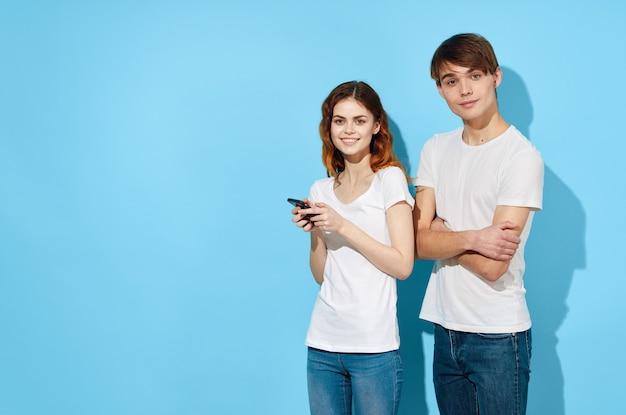 Vrolijk jong stel in witte t-shirts telefoons in handen communicatie levensstijl