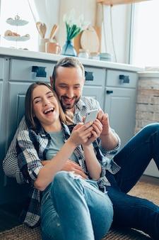 Vrolijk jong stel knuffelen op de keukenvloer en een jonge dame lacht