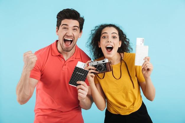 Vrolijk jong stel staat geïsoleerd en toont paspoorten met vliegtickets