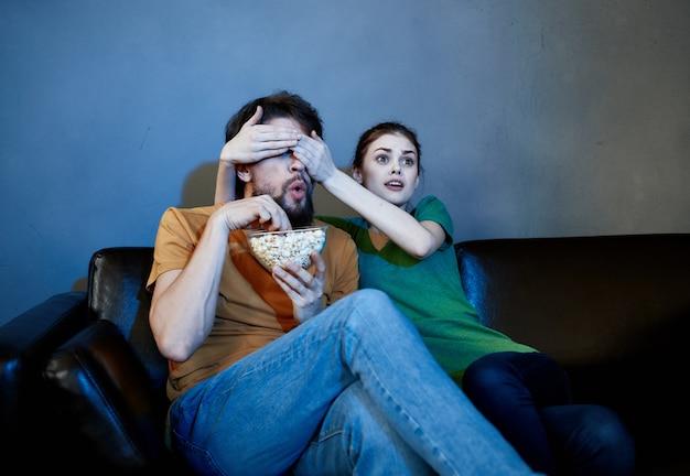 Vrolijk jong stel thuis tv kijken 's avonds ontspanning