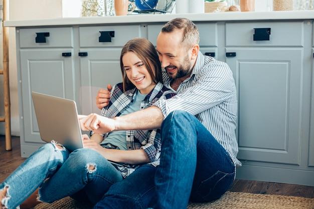 Vrolijk jong stel zittend op de vloer en kijkend naar het scherm van een moderne laptop