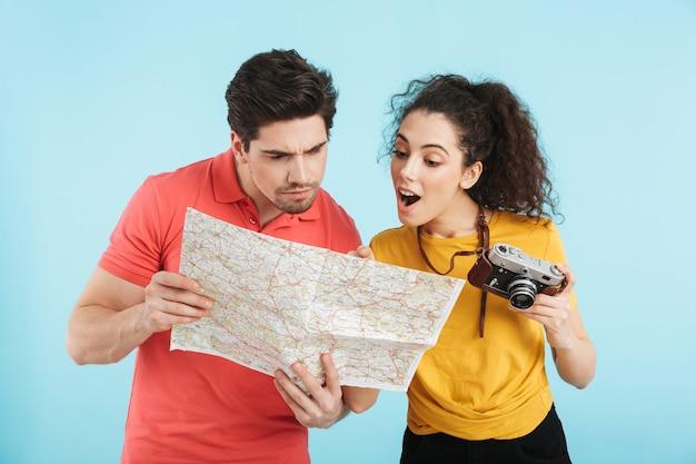 Vrolijk jong toeristenpaar dat geïsoleerd staat, kaart onderzoekt, fotocamera vasthoudt