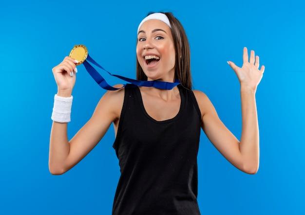 Vrolijk jong vrij sportief meisje dat hoofdband en polsbandje en medaille draagt rond de medaille van de nekholding en het tonen van lege die hand op blauwe ruimte wordt geïsoleerd