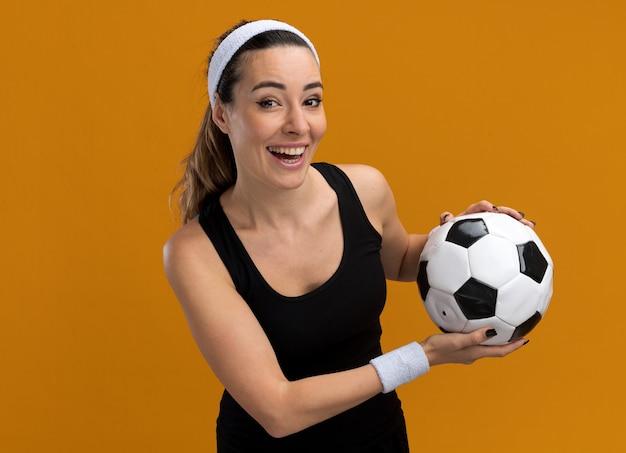 Vrolijk jong, vrij sportief meisje met een hoofdband en polsbandjes met voetbal geïsoleerd op een oranje muur met kopieerruimte