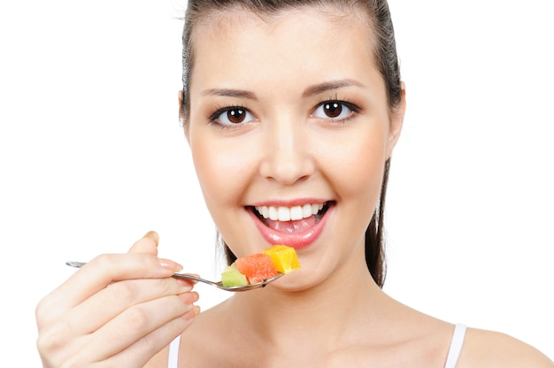 Vrolijk jong vrouwelijk gezicht met lepel met stukjes fruit
