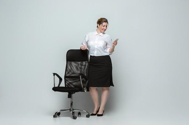 Vrolijk. jonge vrouw in kantoorkleding. lichaamspositief vrouwelijk karakter, feminisme, van zichzelf houden, schoonheidsconcept. plus grootte zakenvrouw op grijze muur. baas, mooi. inclusie, diversiteit.