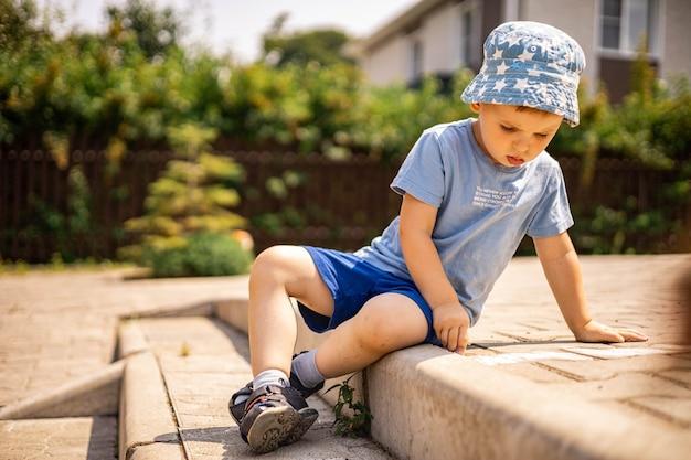 Vrolijk jongetje dat hinkelen met krijt op de grond trekt en geniet van een gelukkige jeugd in de achtertuin