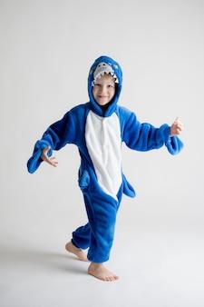 Vrolijk jongetje die zich voordeed op een witte achtergrond in pyjama, blauw haaikostuum