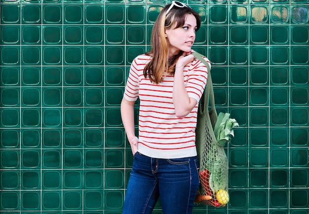 Vrolijk kaukasisch jong meisje met een netzak over haar schouder met groenten op een groene muur in de straat