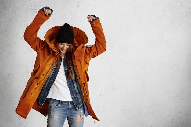 Vrolijk kaukasisch meisje dat stijlvolle winterkleren draagt die met haar handen omhoog in de lucht dansen