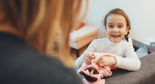 Vrolijk kaukasisch meisje en haar moeder die een stuk speelgoed in nieuwe kleren verkleden