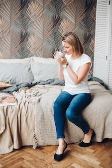 Vrolijk kaukasisch meisje met blond haar, wit t-shirt, jeans zit in de grote lichte kamer en drinkt koffie