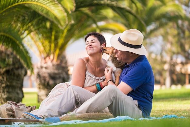 Vrolijk kaukasisch stel dat geniet van vrijetijdsbesteding in de buitenlucht, zittend op het groene gras in de stad en speelt met jonge gekke shetlandhond die veel kust. liefde en alternatieve familie en vriendschap