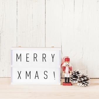 Vrolijk kerstboodschap met notenkraker en denneappels