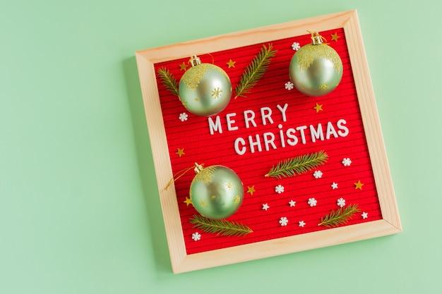 Vrolijk kerstfeest 2022. rood letterbord met groetcitaat en groene kerstballen versierd met dennentakken. platliggend, bovenaanzicht