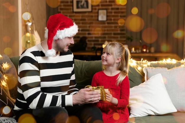 Vrolijk kerstfeest en een gelukkig nieuwjaar. cadeau verrassing. een klein blij lachend dochtermeisje opent met verbazing een kerstcadeau. vader geeft zijn dochter cadeau binnenshuis in feestelijk versierd huis