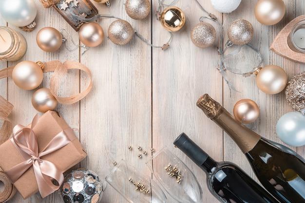 Vrolijk kerstfeest en een gelukkig nieuwjaar. champagne, kerstballen en een cadeau op een beige achtergrond. bovenaanzicht, kopieer ruimte.