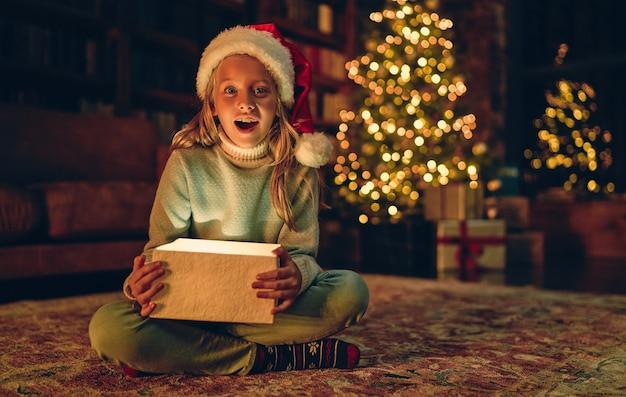 Vrolijk kerstfeest en een gelukkig nieuwjaar! charmant klein meisje zit thuis met open geschenkdoos. magisch licht van binnenuit.