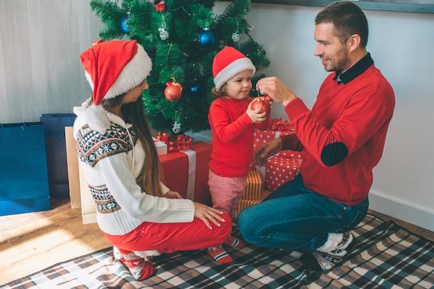 Vrolijk kerstfeest en een gelukkig nieuwjaar. gelukkige familie samen zitten op de kerstboom. jonge man houdt rode speelgoed vast terwijl kleine meid het hele ding heeft. ze is geconcentreerd. vrouw kijk naar hen