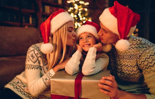 Vrolijk kerstfeest en een gelukkig nieuwjaar! gelukkige familie wacht op het nieuwe jaar in santa claus-hoeden die geschenken met elkaar uitwisselen. mama en papa kussen een schattige dochter