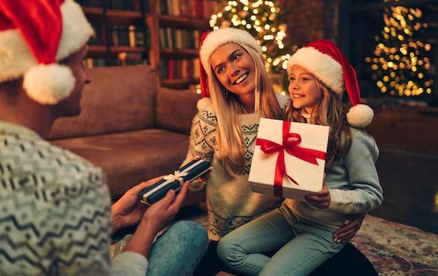 Vrolijk kerstfeest en een gelukkig nieuwjaar! gelukkige familie wacht op het nieuwe jaar in santa claus-hoeden die geschenken met elkaar uitwisselen.