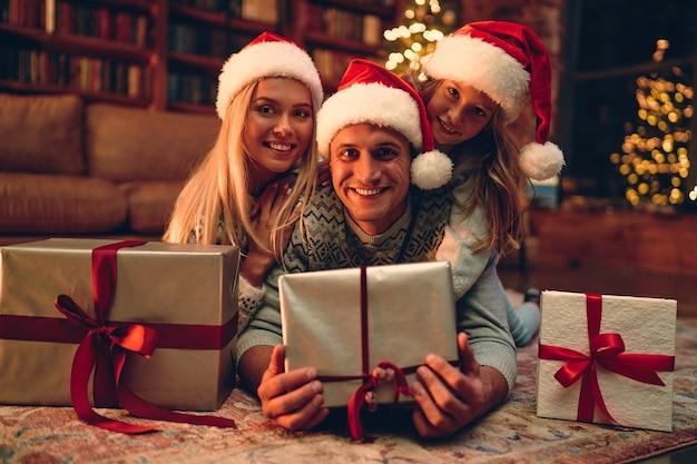 Vrolijk kerstfeest en een gelukkig nieuwjaar! gelukkige familie wacht op het nieuwe jaar in santa claus-hoeden op de grond liggen en hun geschenkdozen vasthouden.