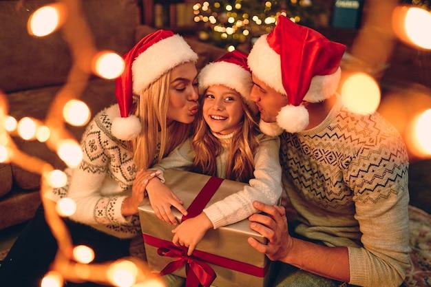 Vrolijk kerstfeest en een gelukkig nieuwjaar! gelukkige familie wacht op het nieuwe jaar in santa claus-hoeden wisselen geschenken met elkaar uit. papa en mama kussen een schattige dochter